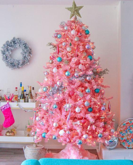 un albero di Natale rosa caldo con decorazioni e luci neutre, metalliche e blu