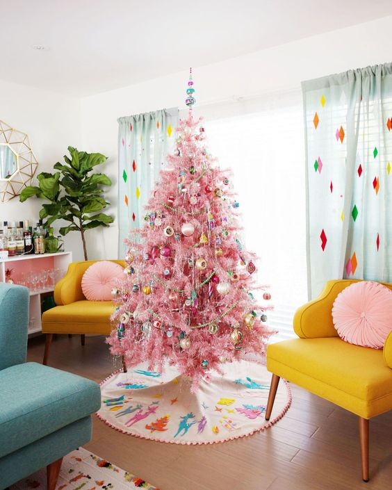 un albero di Natale rosa con ornamenti retrò colorati, ghirlande e ghirlande di perline aggiunge ancora più colore