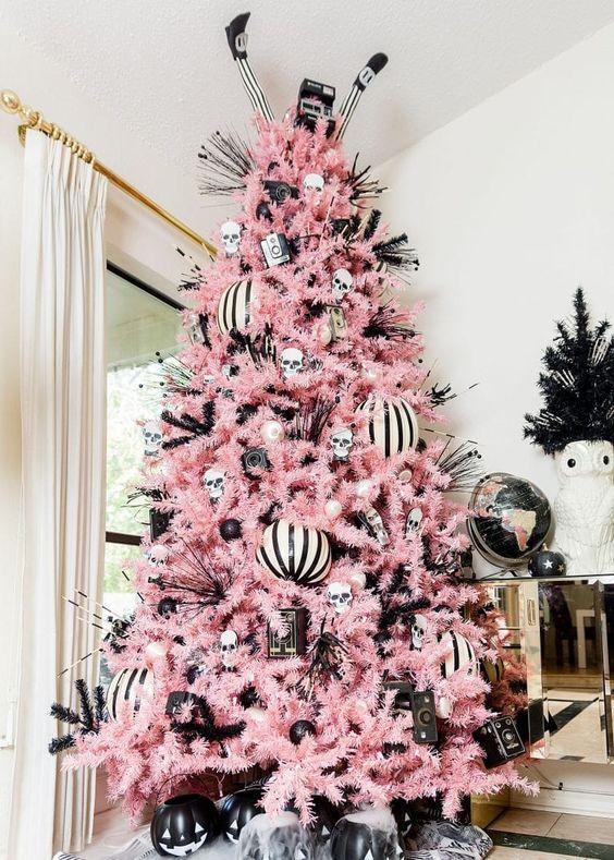 un albero di Natale rosa pastello con ornamenti in bianco e nero, teschi, gambe di streghe e una macchina fotografica vintage per un albero ispirato ad Halloween