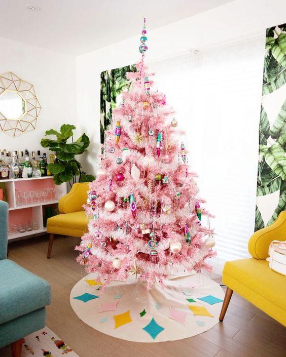 un albero di Natale rosa decorato con ornamenti pastello e colorati e roba soffice oltre a un brillante topepr sembra retrò