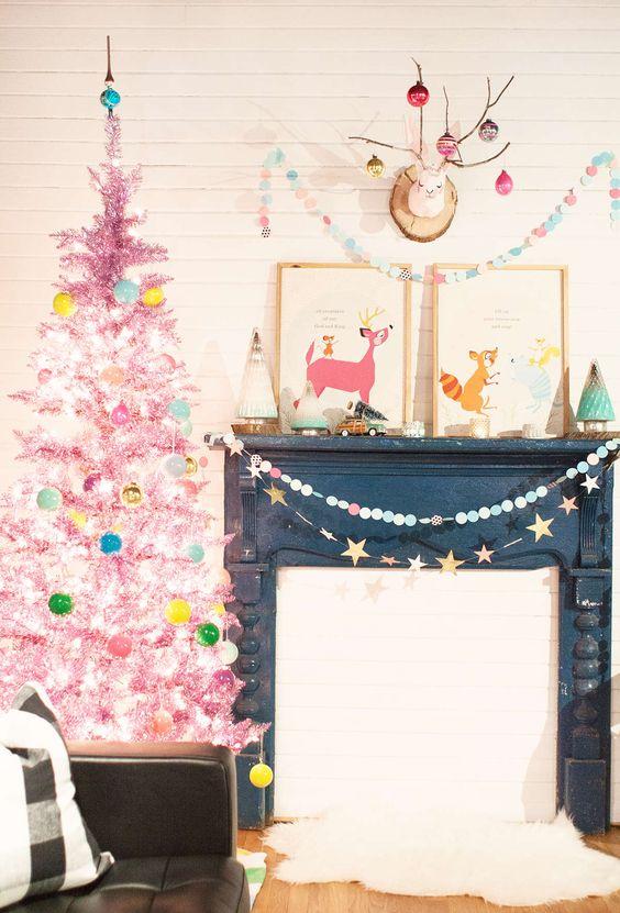 un albero di Natale in orpello rosa caldo con luci e ornamenti colorati è un tocco luminoso per il tuo spazio per le vacanze