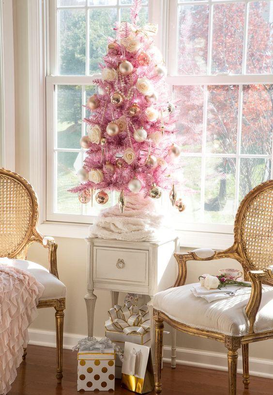 un albero di Natale rosa con ornamenti d'oro, perline d'oro e rose più un fiocco in cima sembra raffinato e vintage