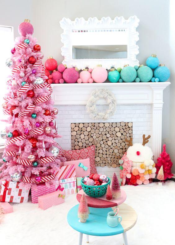 un albero di Natale rosa con nastri a strisce e ornamenti metallici e luminosi di grandi dimensioni oltre a quelli abbinati sulla mensola del camino