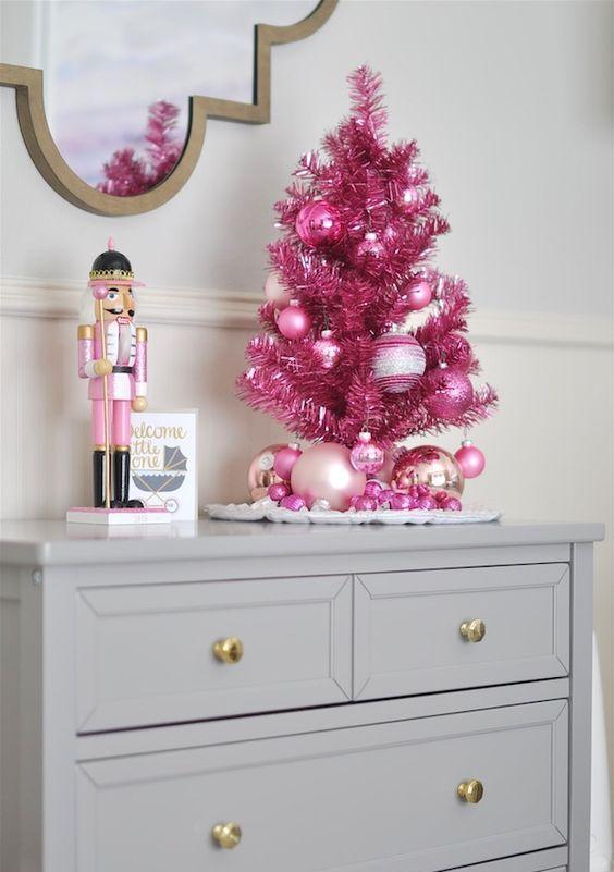 un minuscolo albero di Natale in orpello rosa caldo con ornamenti glitter rosa brillanti è una bella versione da tavolo di un solito