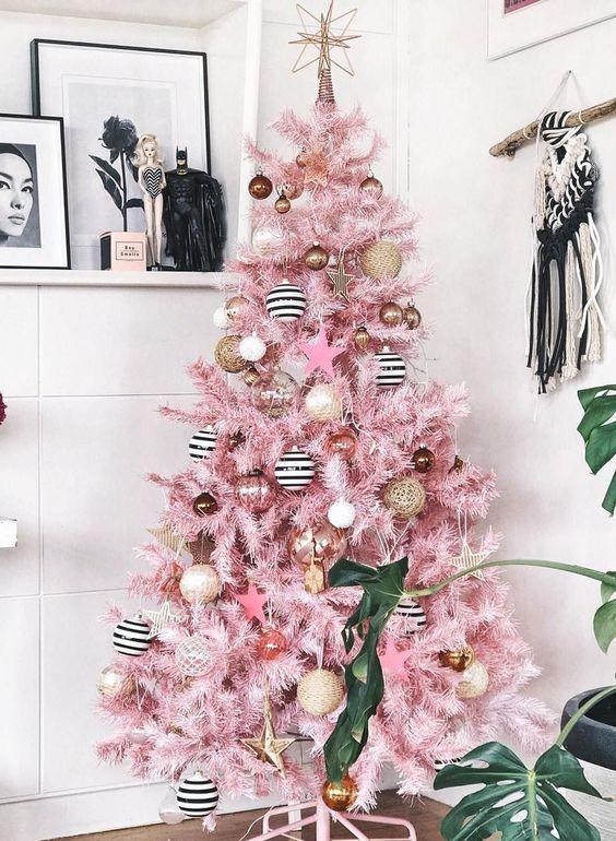 un albero di Natale rosa con vite, ornamenti in bianco e nero, quelli in rame e oro e un cappello a cilindro a stella
