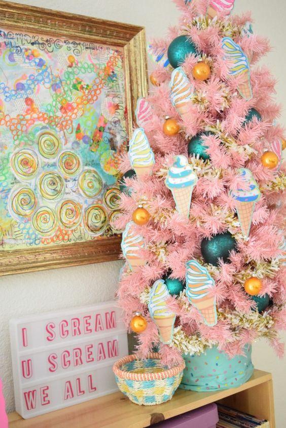 un albero di Natale rosa da tavolo con decorazioni di gelato, calendula e verde acqua di varie dimensioni