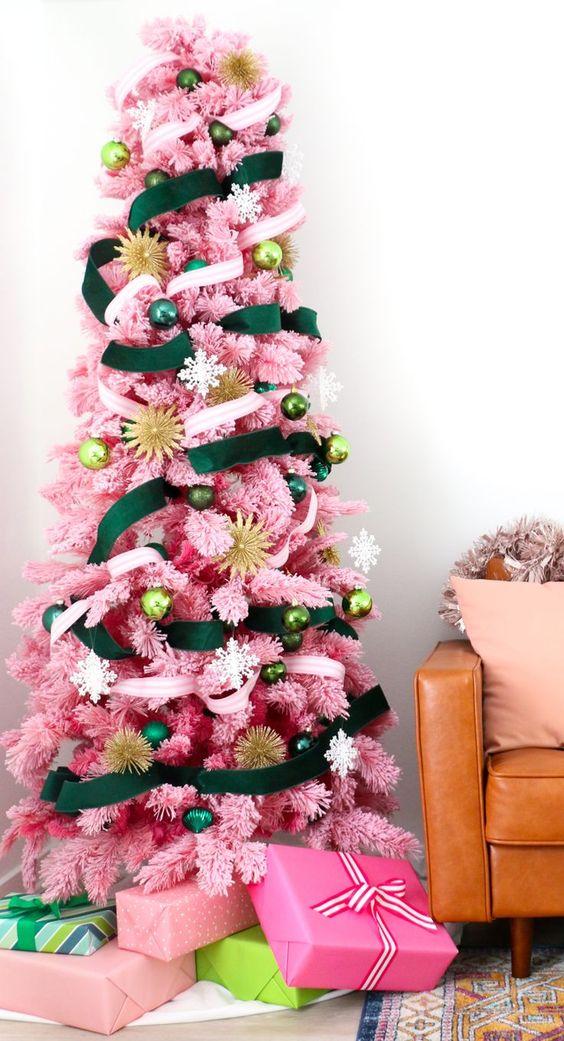 un albero di Natale rosa con nastri smeraldo e neutri e ornamenti in varie tonalità di verde più tocchi d'oro