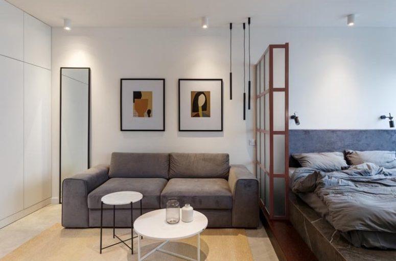 Il soggiorno è separato dalla camera da letto con una mezza parete in vetro satinato
