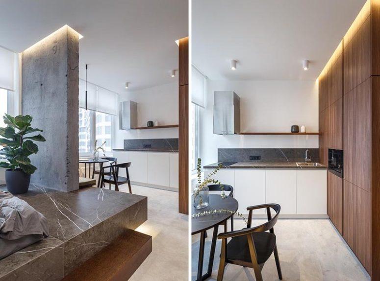 La cucina è realizzata con armadi bianchi e un piano di lavoro grigio stoen più uno scaffale aperto