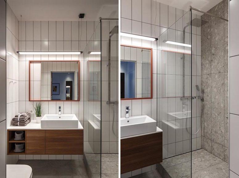 Il bagno è piccolo e semplice, con piastrelle bianche e un lavabo sospeso più uno spazio doccia nell'angolo