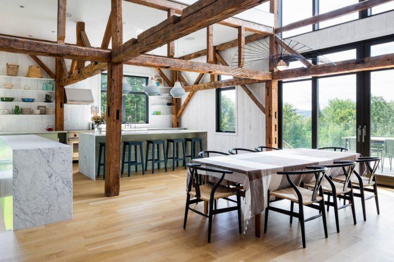 La cucina e la sala da pranzo sono posizionate l'una accanto all'altra, con isole cucina in marmo, mensole bianche e comode sedie