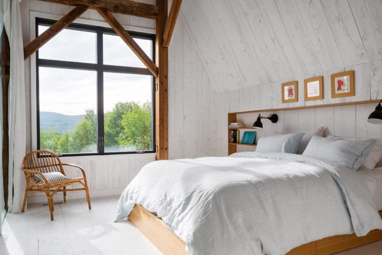 La camera da letto presenta una testiera incorporata, un letto, alcune mensole galleggianti e una grande finestra