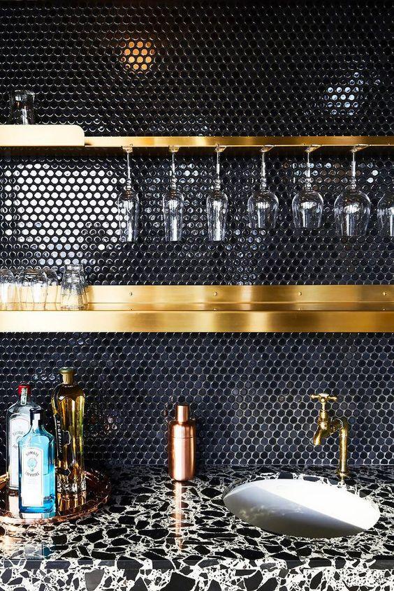 un paraschizzi di piastrelle nere penny e ripiani e infissi dorati compongono una combinazione molto chic e raffinata