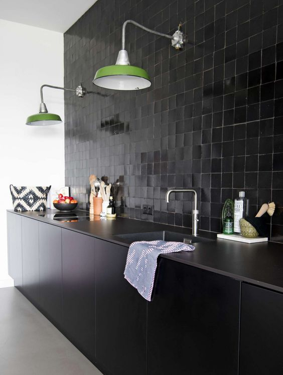 un paraschizzi di piastrelle smaltate nere, controsoffitti in pietra ed eleganti armadi neri più lampade da parete verdi