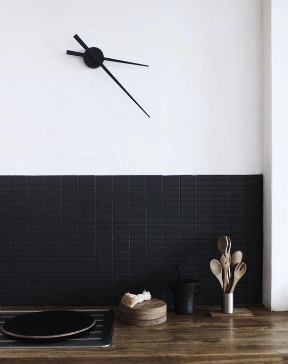 un paraspruzzi super contemporaneo con piastrelle lunghe e strette nere opache contrasta con il blocco macellaio di colore chiaro