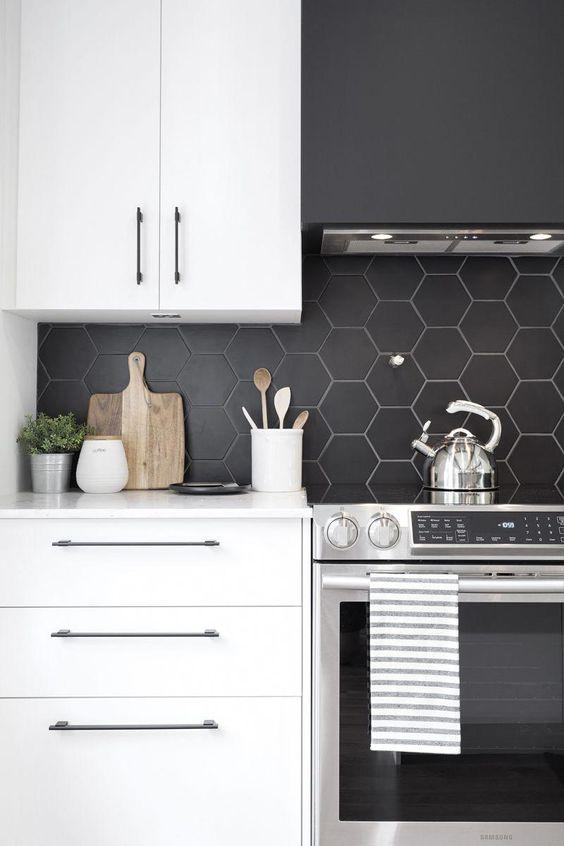 una cucina bianca minimalista con un paraschizzi di piastrelle esagonali nero opaco, che è accentuato da malta bianca