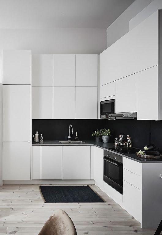 un'elegante cucina bianca con alzatina in piastrelle nere di grandi dimensioni che contrasta e risalta molto