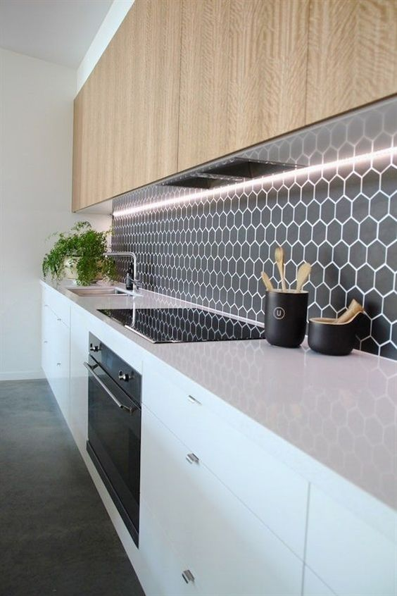 un paraschizzi nero minimalista con piccole piastrelle esagonali evidenziate con malta bianca