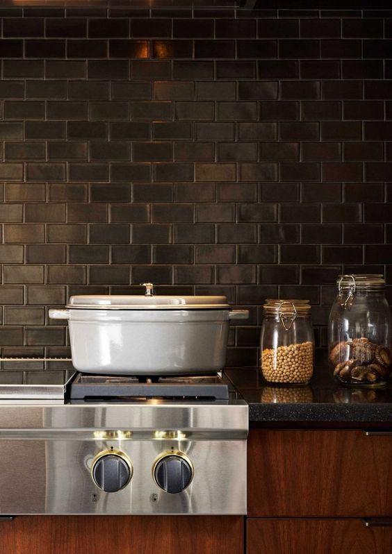 armadi dai toni ricchi, controsoffitti in pietra grigia e piastrelle nere della metropolitana per il backsplash compongono una cucina vintage