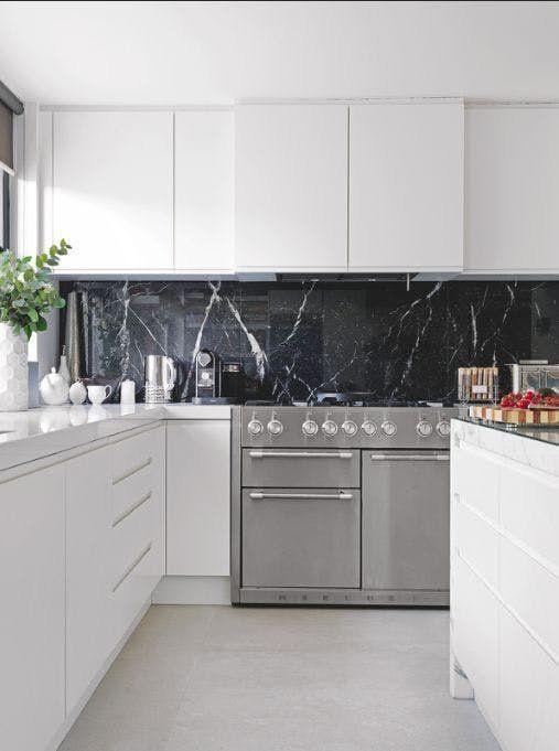 una cucina minimalista bianco puro con un alzatina in marmo nero che aggiunge un tocco raffinato e chic