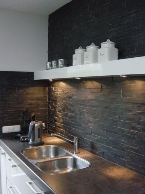 un paraschizzi cucina in finta pietra nera con luci aggiuntive è un'idea fresca ed elegante per una cucina contemporanea