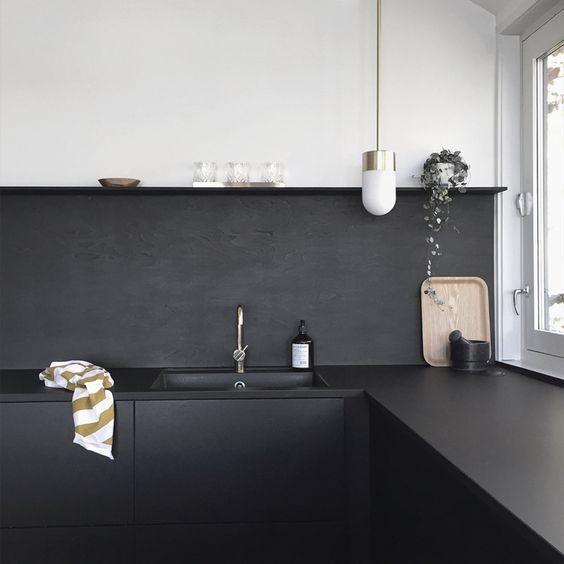 un paraschizzi verniciato nero opaco è un'idea a basso costo e continua l'arredamento della cucina con armadi e controsoffitti neri