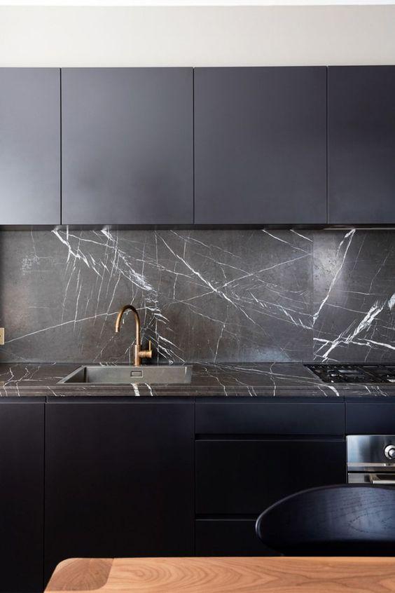 una cucina minimalista blu notte con armadi eleganti, alzatine in marmo nero e controsoffitti più infissi in ottone