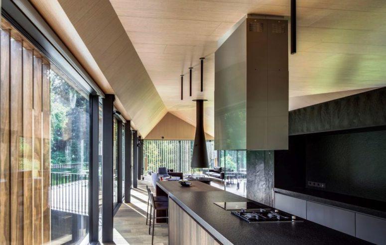 un paraschizzi in metallo nero e un piano di lavoro coordinato contribuiscono a creare un design della cucina minimalista e lunatico
