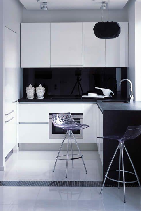 una piccola cucina minimalista in bianco e nero con un elegante alzatina in vetro nero che rende il contrasto più forte