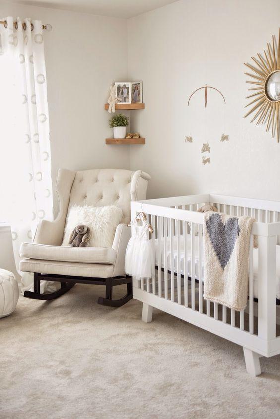 un cameretta neonato neutro chic con una sedia a dondolo, una culla semplice, un'opera d'arte raggera, mensole angolari e tessuti stampati