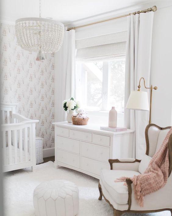 un cameretta neutro chic con un lampadario di perline, una sedia e una culla vintage, un comò, tappeti bianchi e un pouf marocchino