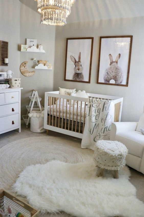 un accogliente cameretta neonato neutro con opere d'arte, una culla, tappeti a strati, uno sgabello con frange e alcuni semplici mobili in legno