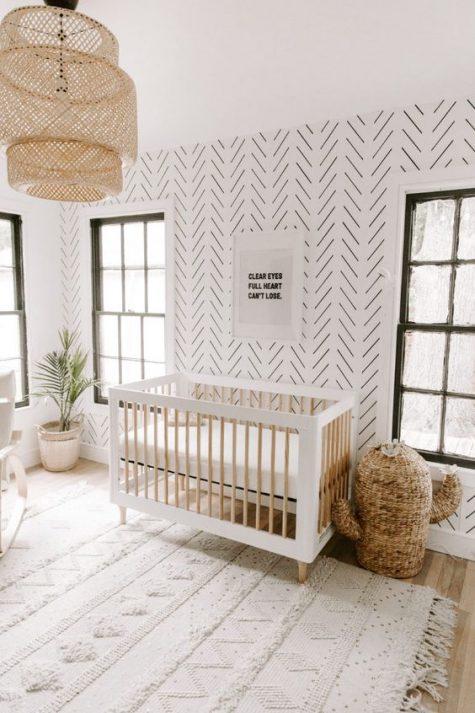 un cameretta minimal boho con pareti di carta da parati, un cactus in vimini per riporre, un paralume in vimini e un tappeto ispirato alle coperte da matrimonio marocchine