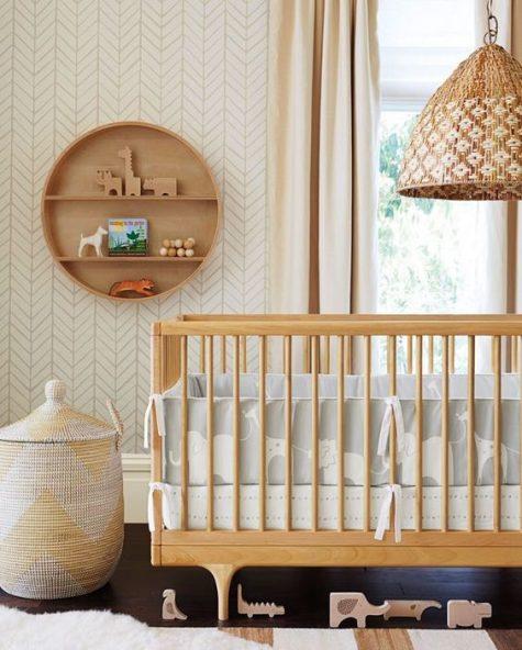 un cameretta neonato moderno della metà del secolo in colori neutri, con mobili in legno, un cestino e una mensola rotonda