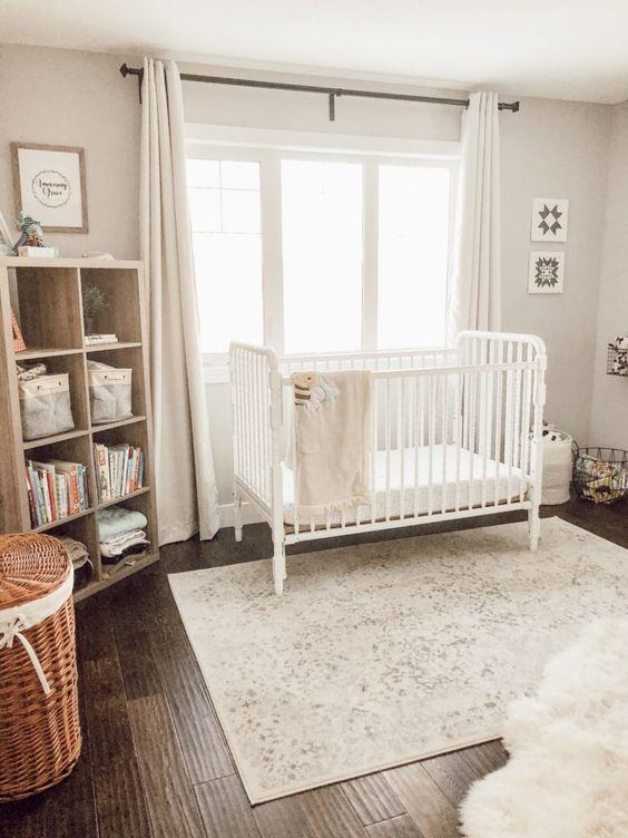 cameretta neutro pieno di luce con una culla, uno scaffale in legno, un tappeto stampato, cestini e tende neutre