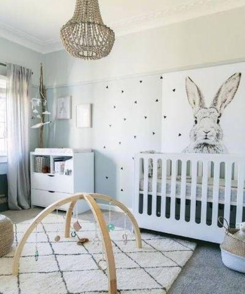 un divertente cameretta neonato neutro con un muro creativo, mobili moderni bianchi, un tappeto stampato, un lampadario di perline e cestini per la conservazione