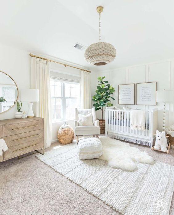 un cameretta neutro e fresco con tappeti a strati, una lampada intrecciata, una culla, un comò di legno e un albero in una cesta
