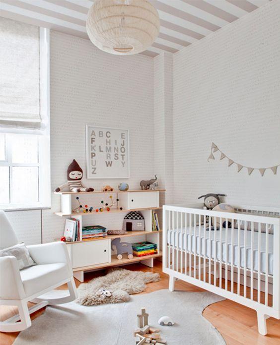 cameretta moderno e neutro con una sedia a dondolo, una culla, una credenza creativa, tappeti e pareti a strisce e un soffitto