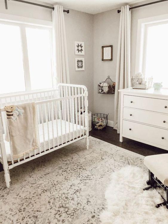 un cameretta neutro con un tappeto stampato, mobili bianchi, mensole in cesto di filo metallico, contenitori e opere d'arte