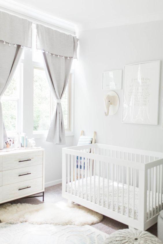 un cameretta neutro con tende grigie, mobili bianchi, tappeti a strati, una galleria a parete con una testa giocattolo