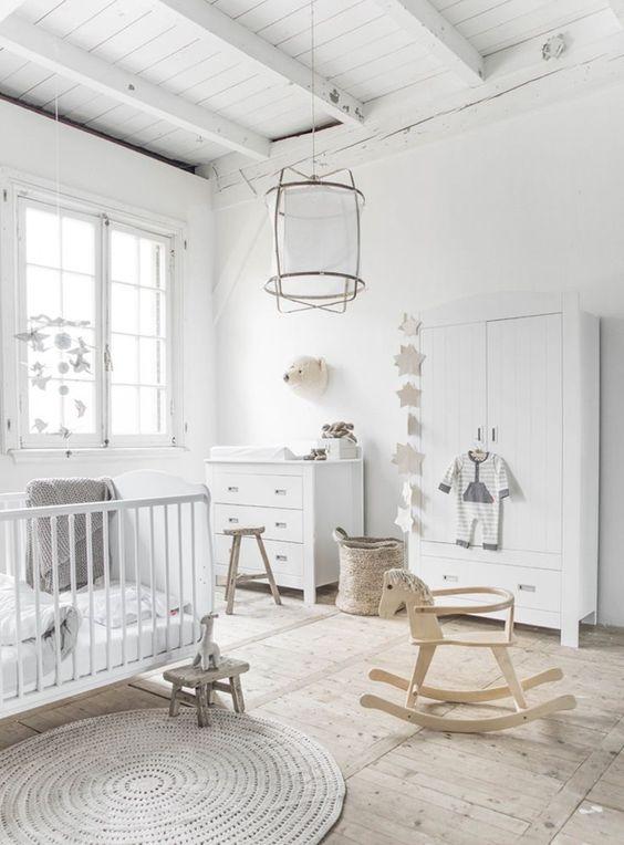 un arioso cameretta neutro con un bel tappeto, cestini, sgabelli in legno, mobili contenitori bianchi e una culla e una bella lampada a sospensione