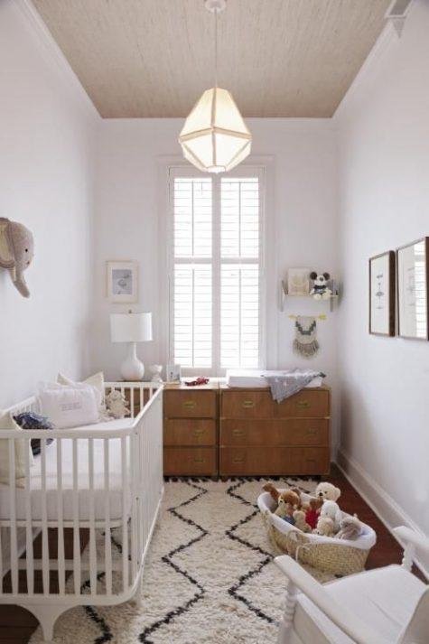 un piccolo cameretta neutro con un tappeto stampato, cassettiere in legno, molti giocattoli e una finta testa di elefante sul muro
