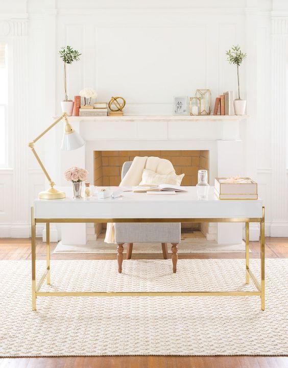 un accogliente studio in casa neutro con un finto camino, una scrivania e una lampada bianche e dorate, piante in vaso e un tappeto stampato più una sedia