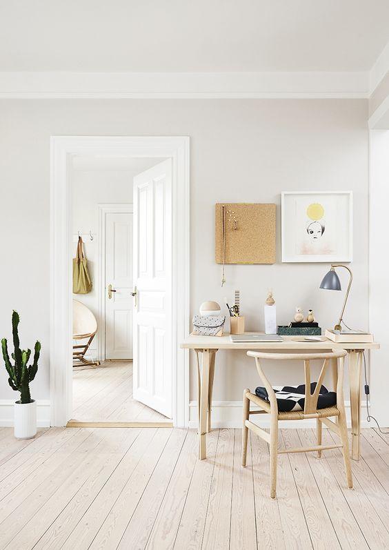 un accogliente ufficio in casa neutro con alcuni mobili in legno, opere d'arte sul muro e un cactus in una pentola