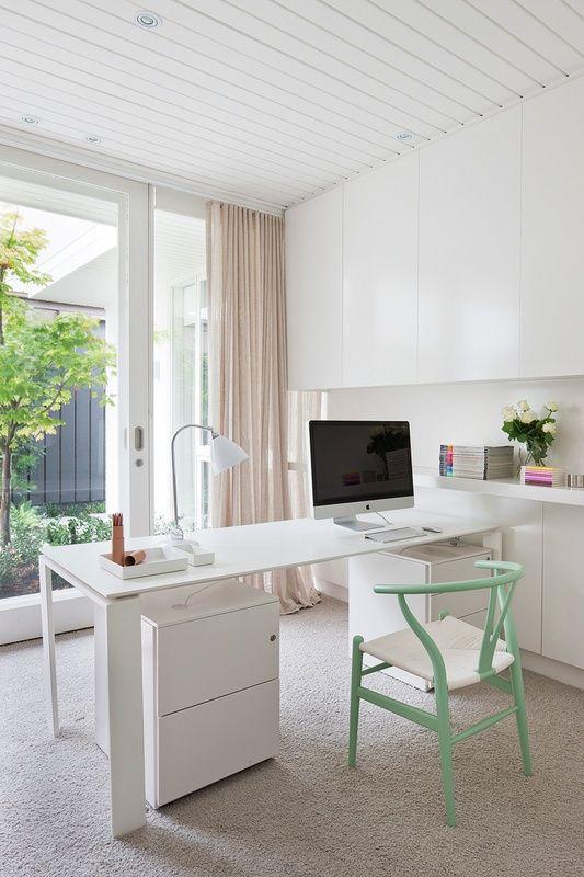 un elegante home office neutro con un mobile contenitore bianco che occupa l'intera parete, una scrivania e una sedia color menta