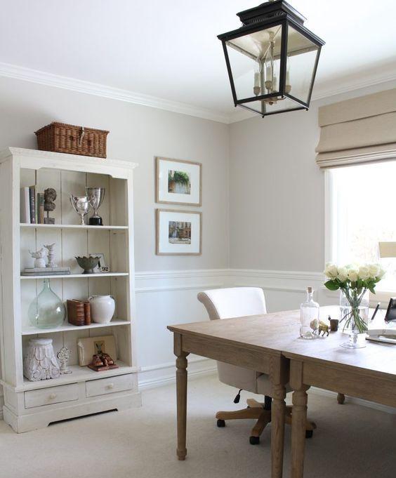 un moderno home office di ispirazione francese con due scrivanie in legno, un buffet neutro per la conservazione e una lampada a sospensione in metallo blakc