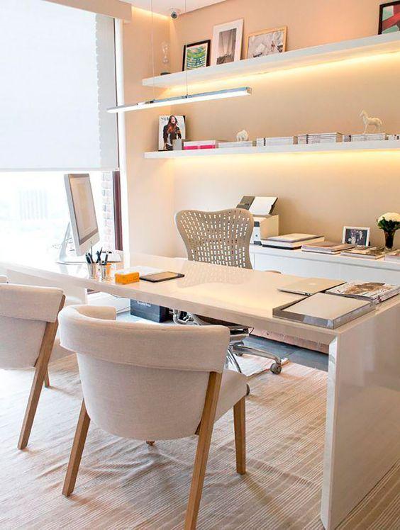 un moderno ufficio in casa neutrla con una scrivania, un mobile contenitore, mensole sospese illuminate e una grande finestra