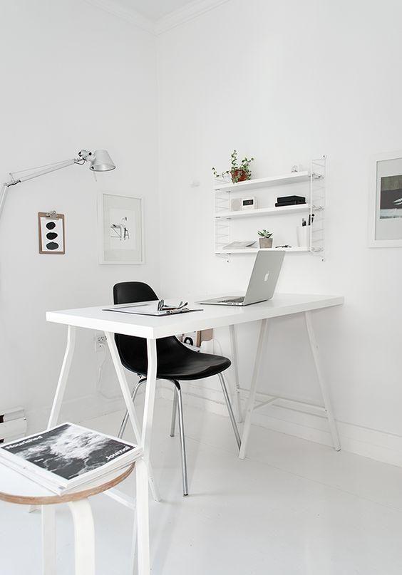 uno spazio di lavoro bianco minimalista con una scrivania bianca, uno scaffale, opere d'arte e un piccolo sgabello accanto alla scrivania