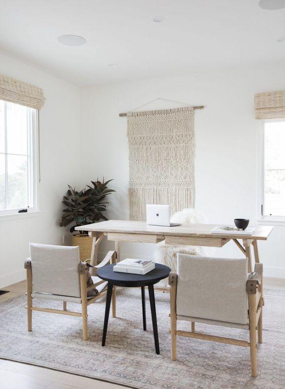 un home office boho neutro e semplice con sfumature intrecciate e un appeso in macramè, una scrivania in legno minimale e sedie abbinate più un tavolino nero
