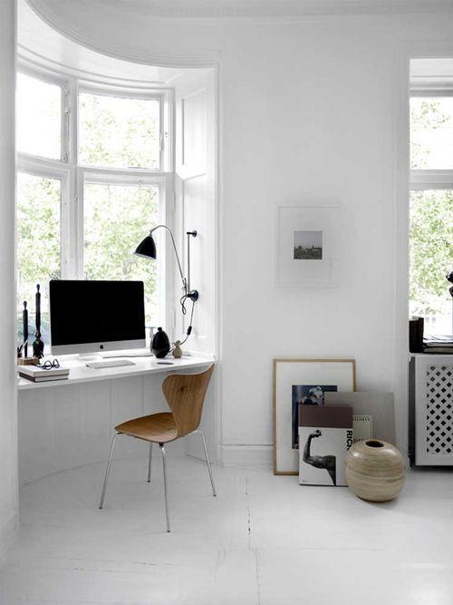 uno spazio di lavoro bianco minimale con una scrivania sul davanzale della finestra, una sedia di legno, alcuni tocchi drammatici di nero e arte